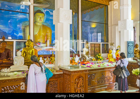 The Buddhist pilgrims pray in Image House of Bodhi Tree Temple - Stock Photo