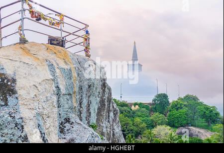 The steep slope of Aradhana Gala Rock with the giant Maha Seya Stupa behind it, Mihintale, Sri Lanka. - Stock Photo