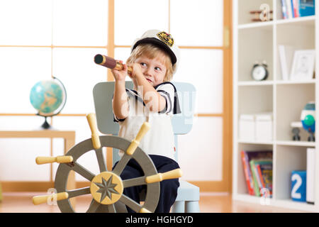 Kid boy dressed captain or sailor plays on chair as ship in his room. Child looks through telescope. - Stock Photo