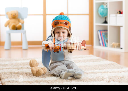 Happy kid boy playing with toy airplane at home in his room - Stock Photo