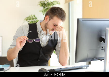 Businessman suffering eyestrain and holding glasses sitting in a desktop at office - Stock Photo