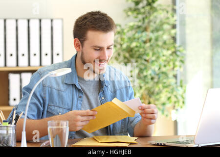 Entrepreneur opening a padded envelope in a desktop at office - Stock Photo