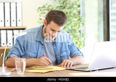 Entrepreneur writing address in a padded envelope before to send it - Stock Photo