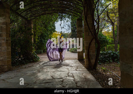 Woman in a beautiful dress dancing in the shadows of the arches - Stock Photo