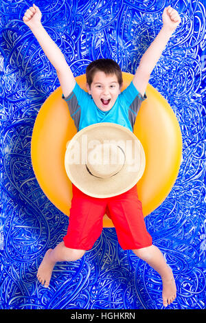 Cheerful little boy celebrating his summer holiday floating in a colorful yellow tube in the pool laughing and extending - Stock Photo
