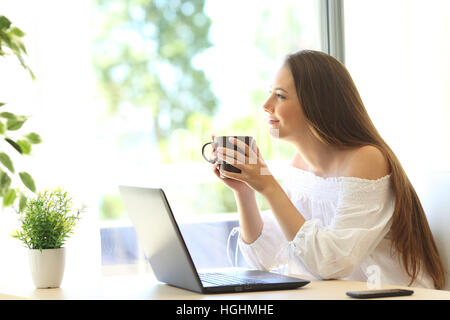 Side view of a pensive housewife with a laptop thinking and holding a coffee cup looking outside through the window - Stock Photo
