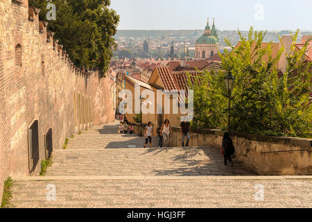 Tourists climb stairs near Hradcany Castle, Malá Strana district, with view on St. Nicholas Church & the City of - Stock Photo