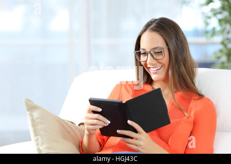 Portrait of a woman reading an ebook with glasses sitting on a couch in the living room at home - Stock Photo