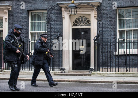 Armed police patrol outside No 10 Downing Street in London. - Stock Photo