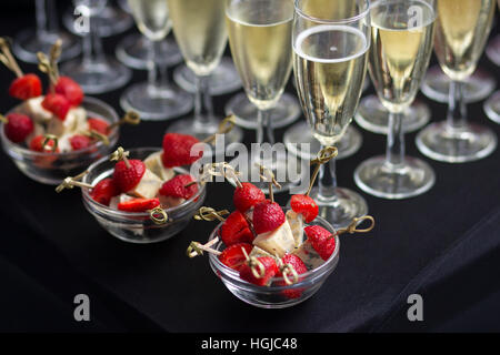 Canapes of cheese and strawberries with champagne - Stock Photo