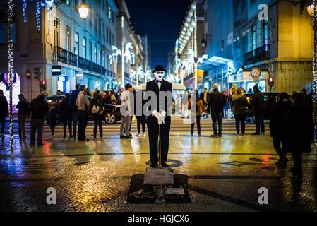 a busker poses as a sad Charlie Chaplin on a wet evening in Rua Augusta, Lisbon, Portugal - Stock Photo