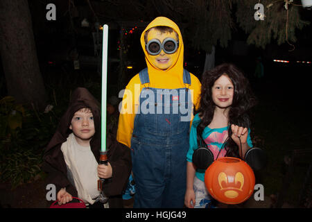 Halloween trick or treat kids in Minion and Jedi Knight costumes carrying a jack-o'-lantern for candy. St Paul Minnesota - Stock Photo