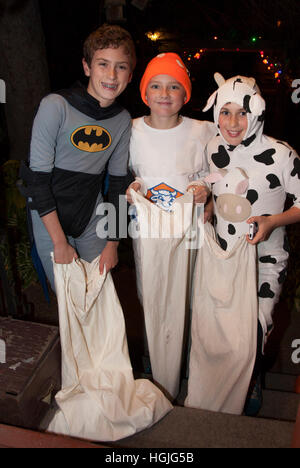 Trick or treaters in Batman and cow Halloween costumes carrying rather large sacks for candy. St Paul Minnesota - Stock Photo
