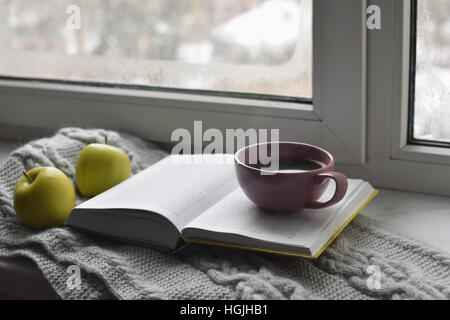 Cozy home still life: cup of hot coffee, green apples and opened book with warm plaid on windowsill against snow - Stock Photo