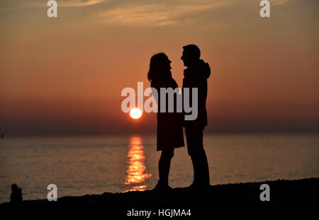 Brighton Sussex, UK. 22nd Jan, 2017. A couple enjoy a romantic moment on Brighton beach as the sun sets behind them - Stock Photo