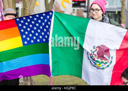 Two young women hold Mexican flag and rainbow US flag in support of womens march, Seattle,USA. - Stock Photo