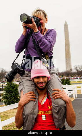 Washington, DC, USA. 21st Jan, 2017. A photographer takes photographs on the shoulders of an unknown while protesters - Stock Photo
