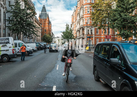 London, United Kingdom - October 17, 2016: People are driving on the street near Kensington gardens in London, England - Stock Photo