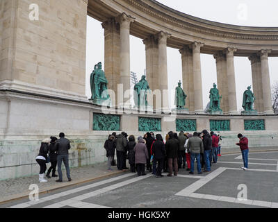 Tourists on Hosok Ter Hero square in Budapest, Hungary, one of the major tourist attractions of the city - Stock Photo
