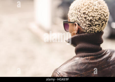 Black woman with short blond afro hair wearing glasses - Stock Photo