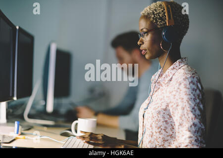 African american woman wearing glasses working on desktop in office - Stock Photo