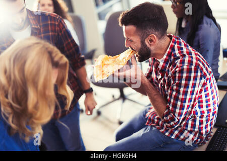 Coworkers eating pizza during work  break at office - Stock Photo