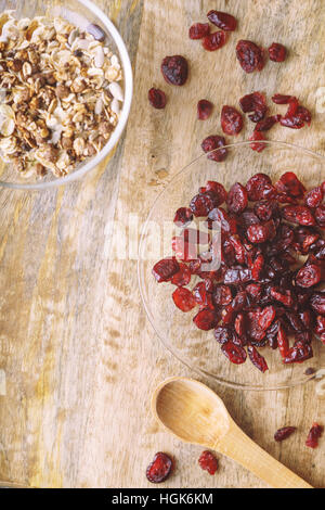 Dried cranberries in the glass bowl on the wooden table top view - Stock Photo