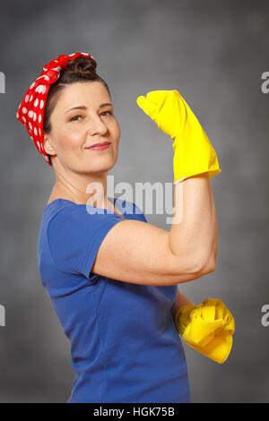 Happy cleaning lady with headscarf, yellow cleaning gloves and cloth, showing her muscles, indicating powerful cleaning - Stock Photo