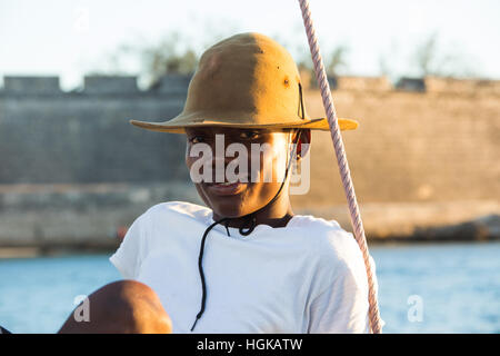 Young man on a dhow in front of the fort, Mozambique Island (Ilha de Mocambique), Mozambique - Stock Photo
