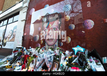 London, UK. 10th January, 2017. Flowers and tributes are placed by an art work of David Bowie on a wall at Brixton, - Stock Photo