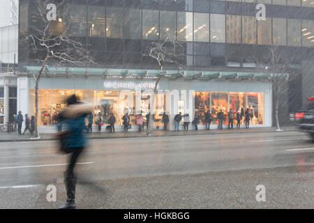 Vancouver, BC, Canada - December 9, 2016 - Transit riders wait along Georgia Street on a snowy morning.  Photo: - Stock Photo