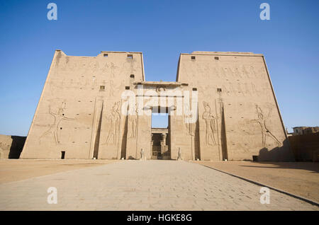 The main entrance of Edfu Temple showing the first pylon, Dedicated to the Falcon God Horus, Located on the west - Stock Photo