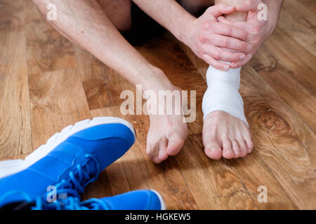 Sportsman massaging his injured ankle after a sport accident - Stock Photo