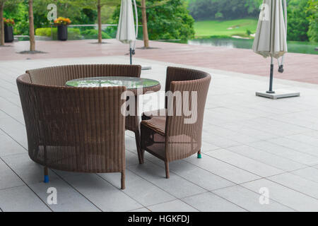 rattan sofa and table set in a garden - Stock Photo