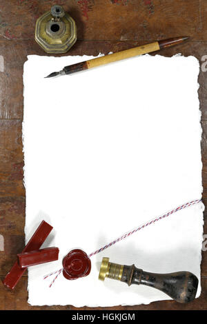 handmade paper with wax seal, dip pen and inkwell on wooden table - Stock Photo