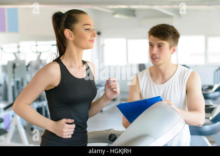Woman running on treadmill at gym and being assisted by personal trainer - Stock Photo