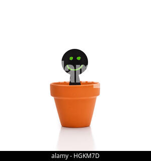 Smiling green and black puppet appears from flower pot - Stock Photo