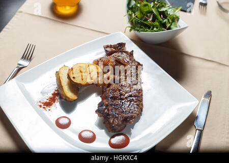 Steak with grilled potatoes with salad side on a white plate - Stock Photo