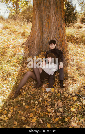 Young couple in a park at autumn, leaning on a tree - Stock Photo