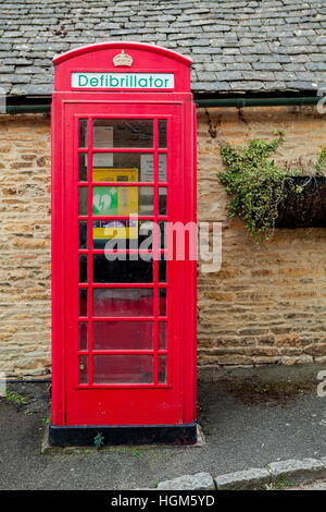 Defibrillator. Old red telephone box now used to keep emergency life saving equipment - Stock Photo