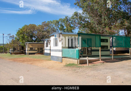 Campground trailer cabin accommodation with trees under a blue sky with clouds in Kalbarri, Western Australia. - Stock Photo