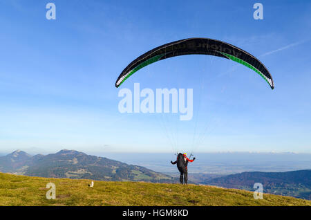 Paraglider taking off from Mont d'Or in France and flying over the Jura mountains - Stock Photo