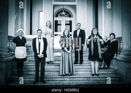 posh english family and servant on steps of stately home - Stock Photo