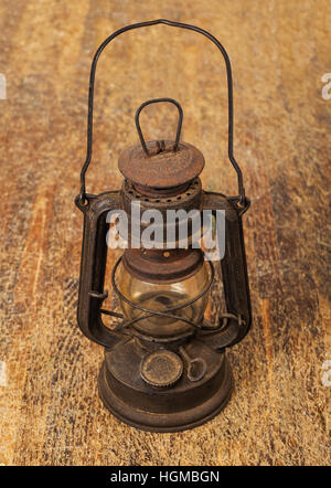 old rusty  lamp on wood background - Stock Photo