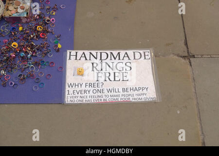 London, UK. 10th January 2017.  Street Artist promotes happiness by inviting passerbys to make and take away rings. - Stock Photo