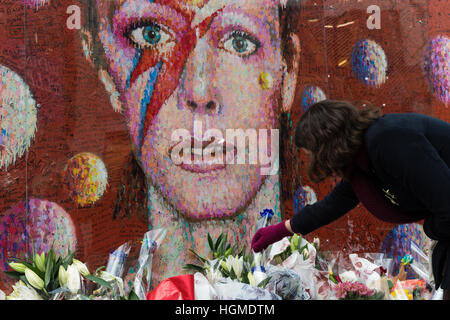 London, UK. 10th January 2017. Fans gather by the mural of David Bowie in artist's birthplace of Brixton to commemorate - Stock Photo