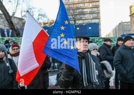 Warsaw, Poland 11th, Jan. 2017 Man holding Polish and European Union flags is seen. Committee for Defence of Democracy - Stock Photo