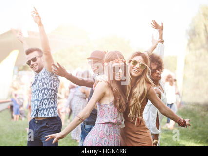 Enthusiastic crowd surfing at music festival - Stock Photo
