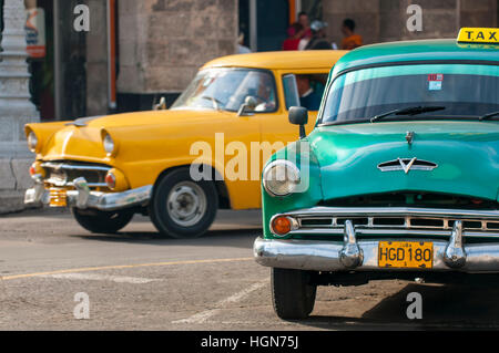 HAVANA - JUNE 13, 2011: Classic American taxi cars, symbols of the historical city, pass on a street in the Centro - Stock Photo