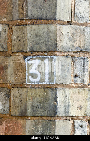 House Number 31 sign painted white on wall - Stock Photo